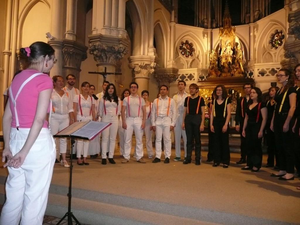 Concert de la chorale de jeunes Incognito de Paris à Notre-Dame des anges. Des choristes en blanc, certains en noir. Chacun avec des bretelles rose, orange, jaune ou rouge